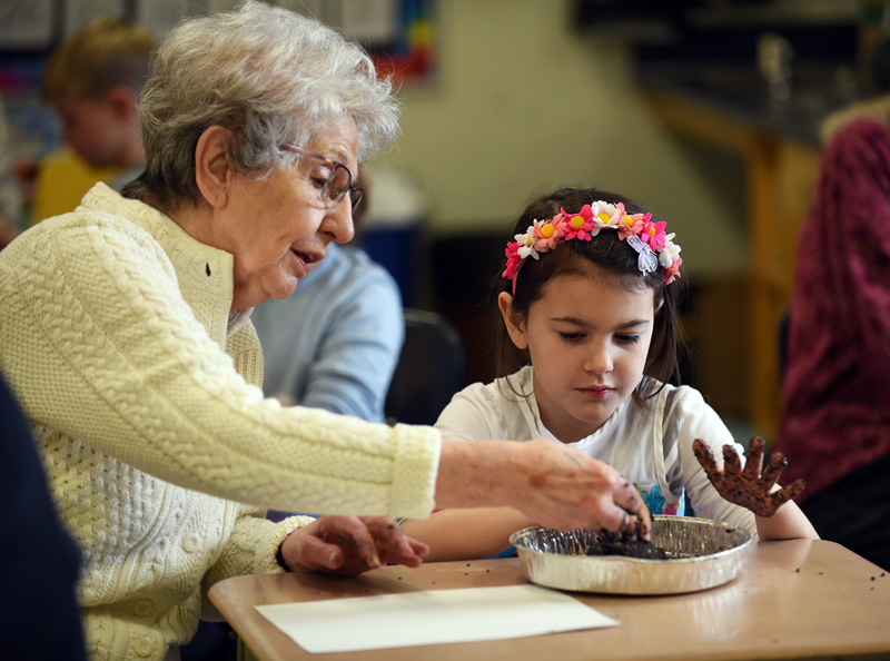 Roberta Atkinson and 8-year-old Rosy Kate Adams make seed balls during a Miles of Friends event at Great Salt Bay Community School in Damariscotta on Wednesday, March 21. (Jessica Picard photo)