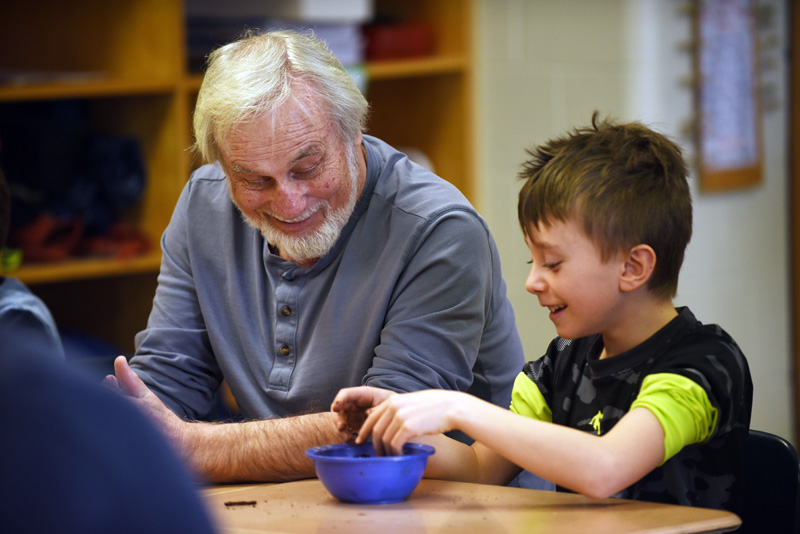 David Caron and 8-year-old Mason Read roll soil into a ball during a seed bomb-making workshop at Great Salt Bay Community School. (Jessica Picard photo)