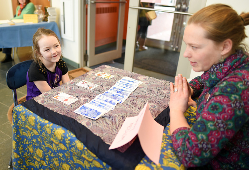 "October Brown, 7, gets her fortune read by Skidompha Library Director of Development and Communications Torie DeLisle during the library's ""A Wrinkle in Time"" event Saturday, March 17. (Jessica Picard photo)"