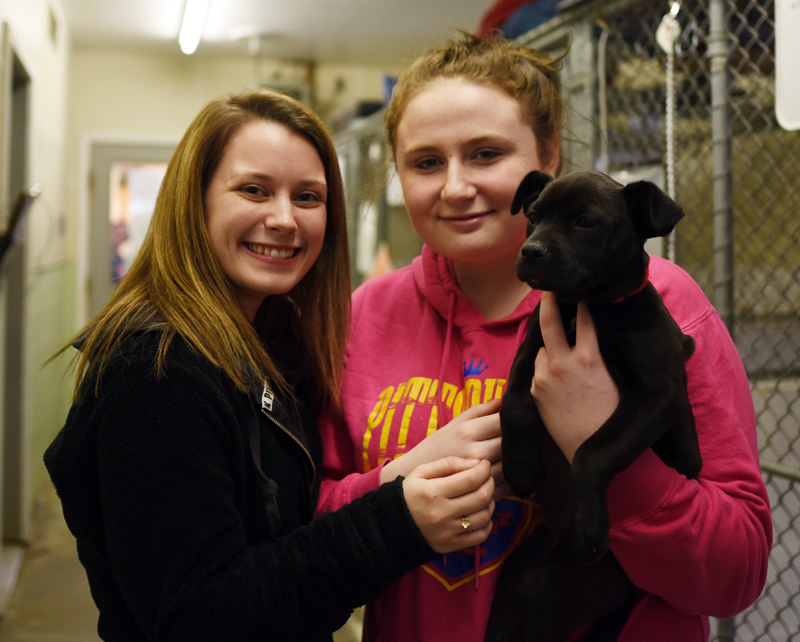 Autumn Sproul (left) and Dakota Beckim hold Sweetie, the 2-month-old puppy they adopted during the Lincoln County Animal Shelter's Puppy Palooza event Saturday, March 3. (Jessica Picard photo)