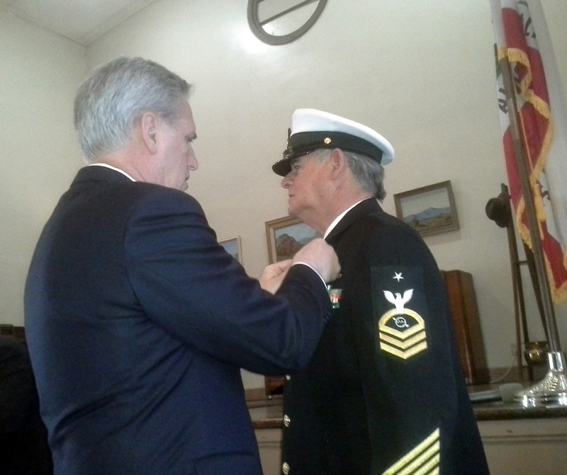 U.S. House of Representatives Majority Leader Kevin McCarthy pins one of many medals on U.S. Navy veteran John Abbott during a special ceremony at the Historic USO building Friday, March 2. (Jessica Weston photo/Daily Independent)