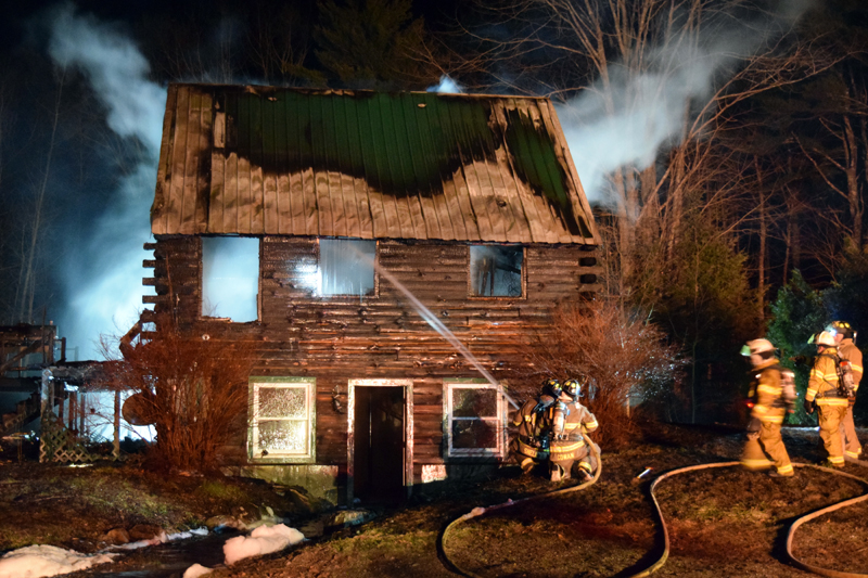 Firefighters attempt to extinguish a blaze at a two-story log cabin at 526 Upper Round Pond Road in Bristol late Sunday, April 15. (J.W. Oliver photo)