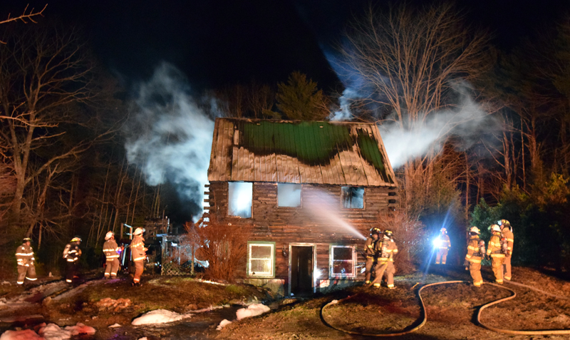 Firefighters surround a burning log cabin at 526 Upper Round Pond Road in Bristol late Sunday, April 15. Bristol Fire Chief Paul Leeman Jr. said the cabin is likely a total loss, but no one was hurt in the fire. (J.W. Oliver photo)