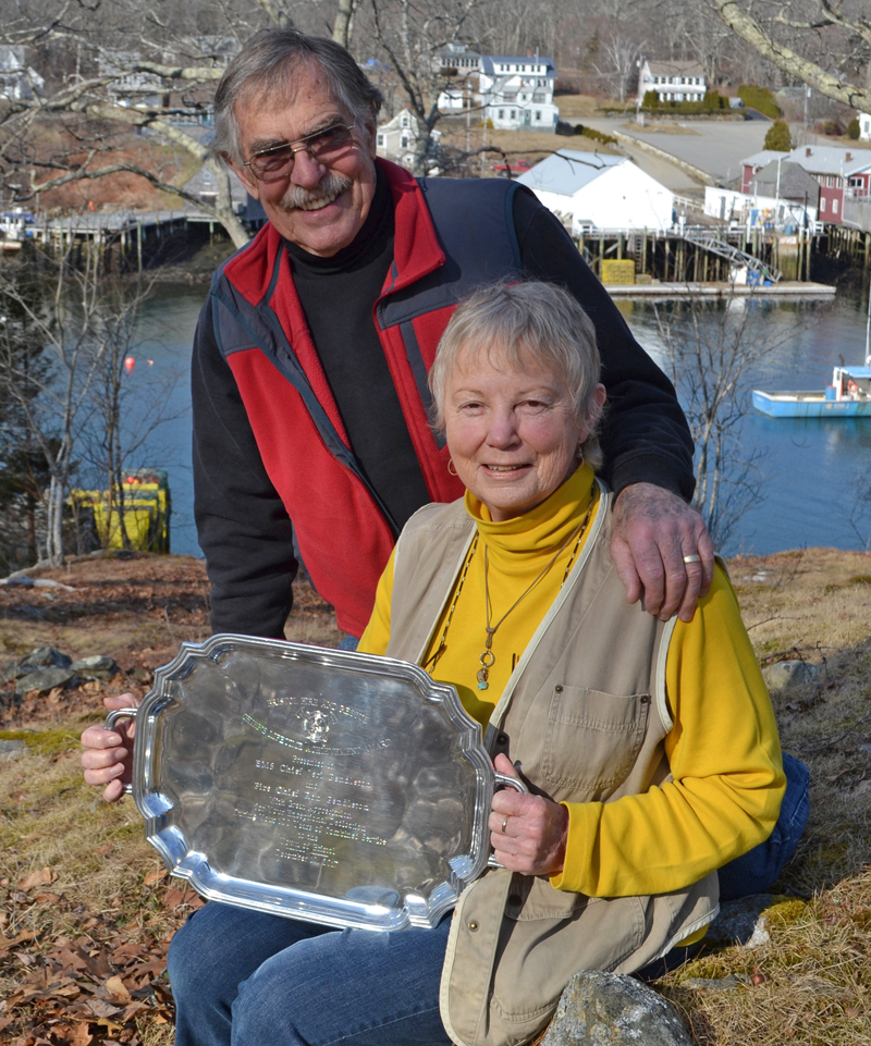 Ron and Jeri Pendleton pose for a photo outside their New Harbor home with a silver platter, a gift in recognition of their 100 years of service to Bristol Fire and Rescue. (Maia Zewert photo)