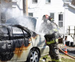Damariscotta firefighter Chris Hilton works to put out a car fire next to the Damariscotta United Methodist Church on Monday, April 23. (Jessica Picard photo)