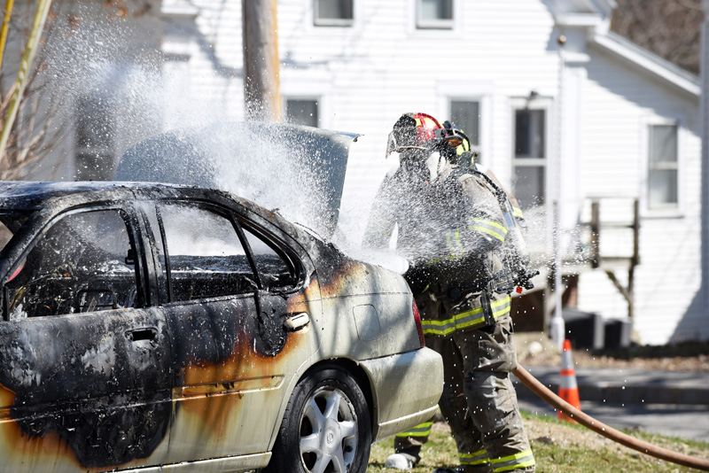 Damariscotta firefighter Chris Hilton works to put out a car fire next to the Damariscotta United Methodist Church on Monday, April 23. (Jessica Picard photo)