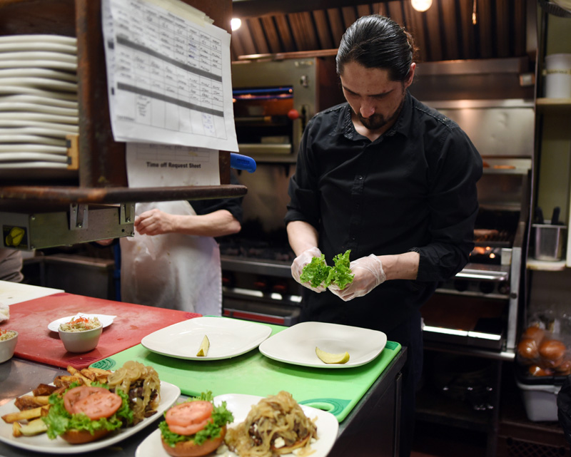 Chef Zack Wiggins prepares food in the kitchen of King Eider's Pub on Monday, April 2. (Jessica Picard photo)