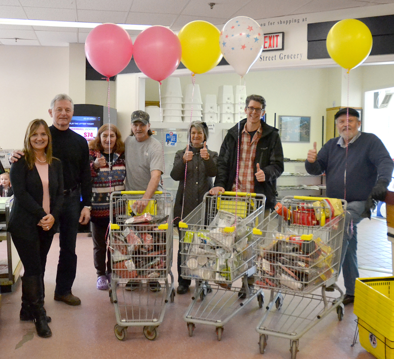 Main Street Grocery owner Jane Gravel and Newcastle Chrysler Dodge Jeep Ram Viper President Randy Miller stand beside the recipients of a 60-second shopping spree Saturday, April 7. From left: Gravel, Miller, Tammy Piper, Paul Gagnon, Lucy Smith, Doug Straus, and the Rev. Tom Wagers. (Maia Zewert photo)