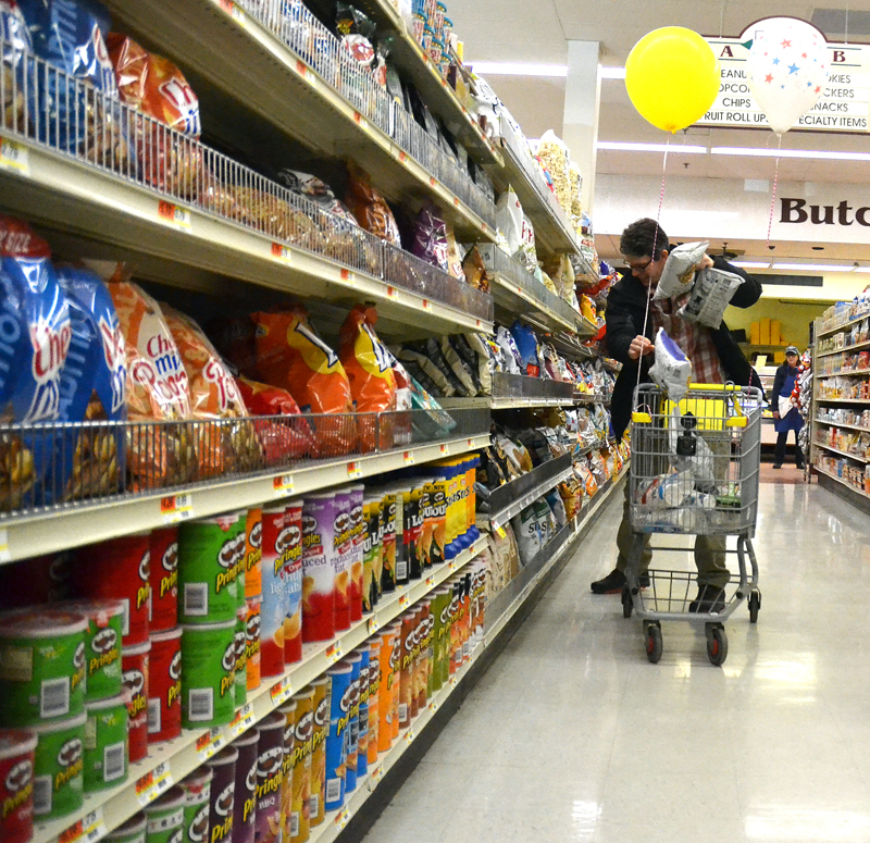 Healthy Kids Board of Directors member Doug Straus flings bags of chips into his cart during a 60-second shopping spree at Main Street Grocery on Saturday, April 7. (Maia Zewert photo)