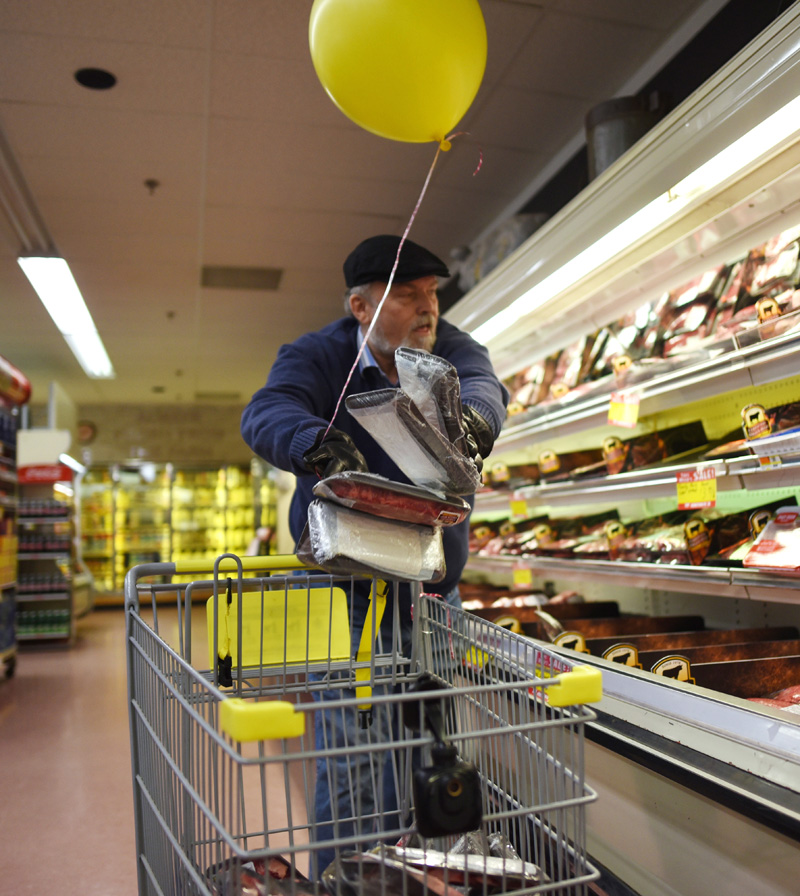The Rev. Tom Wagers, pastor of the Lincoln County Assembly of God, throws meat in his cart during a 60-second shopping spree at Main Street Grocery on Saturday, April 7. (Jessica Picard photo)