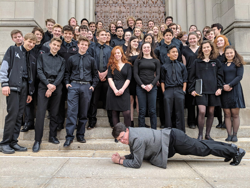 The Lincoln Academy Wind Ensemble on the steps of Riverside Church in New York City, with band director Liz Matta showing off her plank.