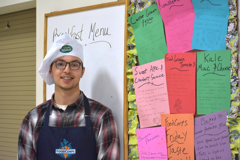 FoodCorps service member Jared Grenier stands next to recipes for a recent FoodCorps Friday at Medomak Middle School in Waldoboro. On FoodCorps Fridays, students taste-test and rate different foods. (Alexander Violo photo)