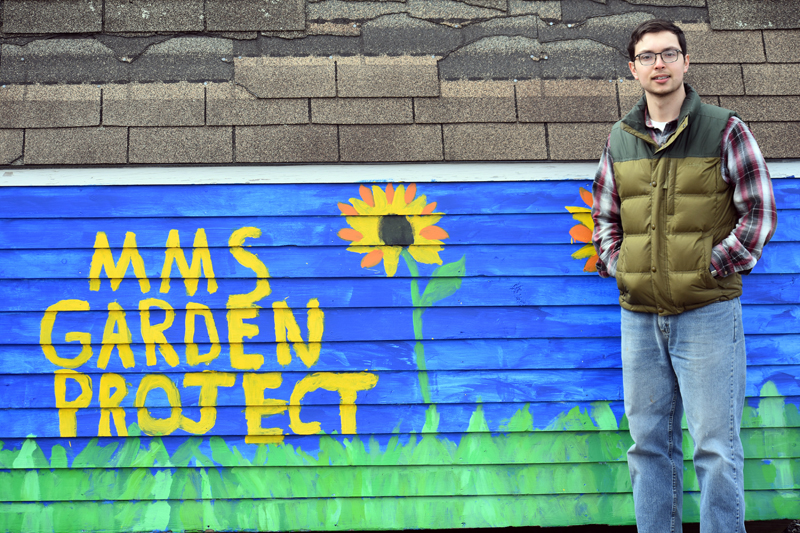 FoodCorps service member Jared Grenier stands next to a sign for the Medomak Middle School garden project. Students painted the sign on a gardening shed. (Alexander Violo photo)