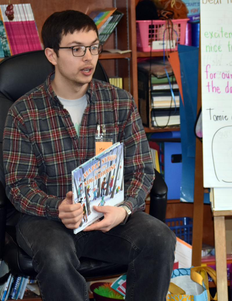 FoodCorps service member Jared Grenier reads a story about maple syrup to second-graders at Miller School in Waldoboro. (Alexander Violo photo)