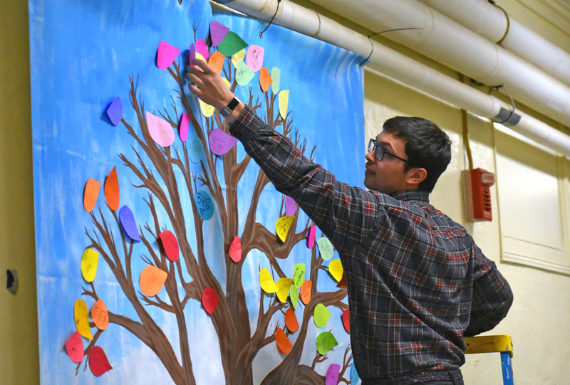FoodCorps service member Jared Grenier helps a student place a leaf on the gratitude tree in the hallway of Miller School in Waldoboro. (Alexander Violo photo)