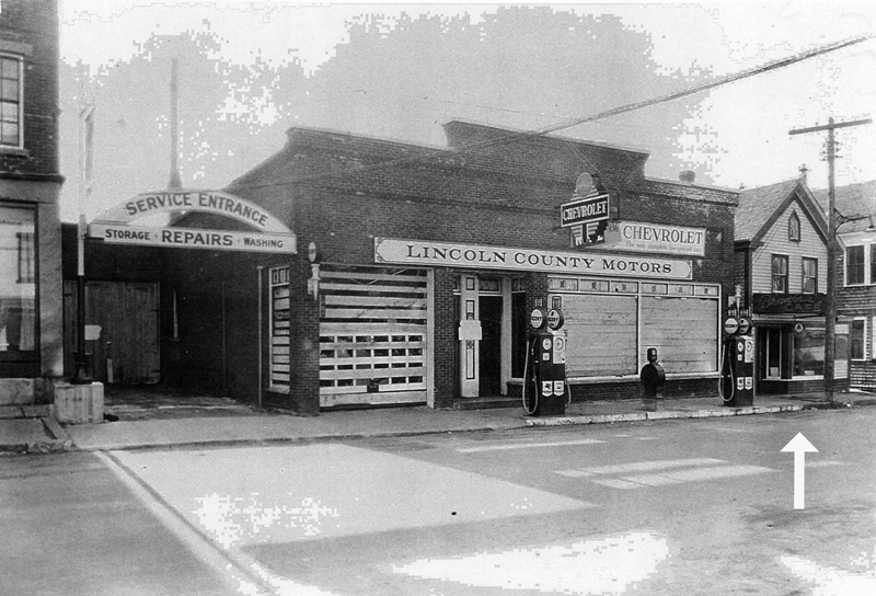 "In this photo, the Frank Carney building had been torn down and now was the location of Lincoln County Motors. It burned in 1932. The small building to the west looking to the bridge, which was Wilbur Knowlton's harness shop, was made over and is Bradford's Cafe; if one looks carefully, the sign over the door says ""Bradford's Cafe."" Paul Bradford was W.G. Knowlton's son-in-law. The arrow points to Paul Bradford's cafe. (Photo courtesy Marjorie and Calvin Dodge)"