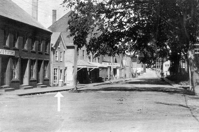 The brick building on the right was built by Mr. Frank Carney. In this photo, it was the location of the Davis Art Photographer Shop in 1897. The small two-story building to the right was owned by Mr. Flint and he had his barbershop there. Then this building became the location of Wilbur George Knowlton's Leather and Harness Shop (the arrow points to the W.G. Knowlton harness shop) for a number of years. After Mr. Knowlton's death, his son-in-law made it into a restaurant. His son-in-law was Paul Bradford. (Photo courtesy Marjorie and Calvin Dodge)