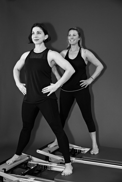 Coaches Darcy Fraser (left) and Virginia Shaw demonstrate the side split on Pilates Reformers.
