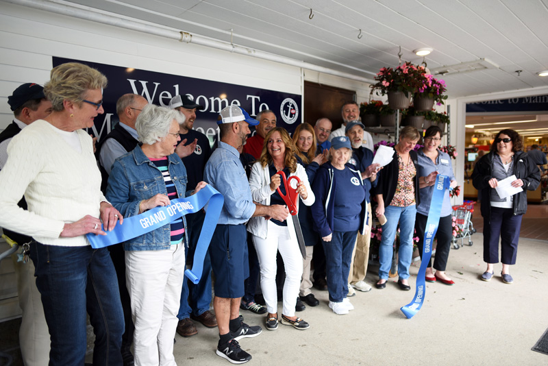 Main Street Grocery owners Gary and Jane Gravel cut the ribbon at the grand opening Friday, May 4, surrounded by employees and members of the Damariscotta Region Chamber of Commerce. (Jessica Picard photo)