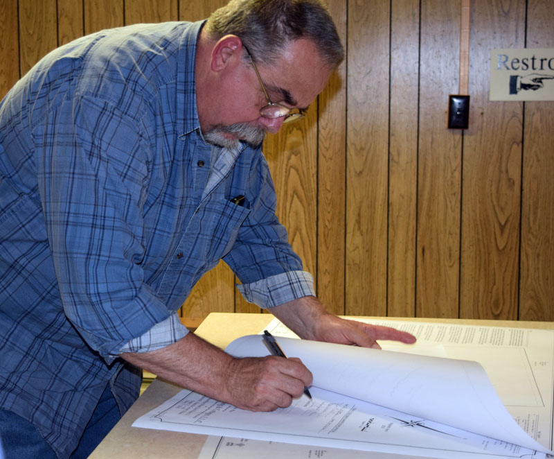 Edgecomb Planning Board alternate Dave Boucher signs the application for a new pub due to open on Route 27. (Jessica Clifford photo)