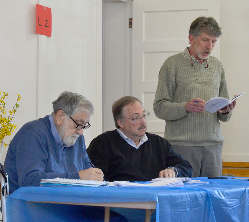 Edgecomb Selectman Mike Smith (right) reads from the town report as Selectmen Jack Sarmanian (left) and Ted Hugger look on during the annual town meeting Saturday, May 19. (Jessica Clifford photo)