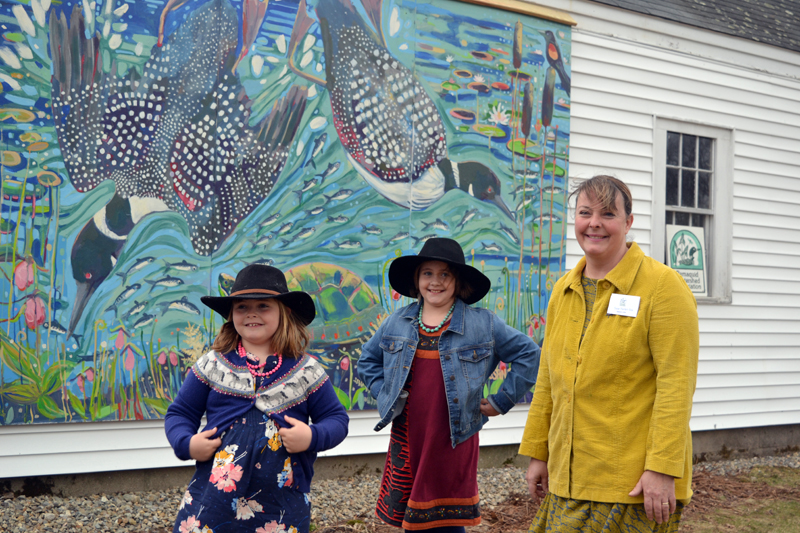 """Susan Bartlett Rice and her daughters, Helen (left) and Amelia, in front of Rice's mural on the Pemaquid Watershed Association office during the reception for Rice's """"Blooms and Loons"""" show April 20. (Christine LaPado-Breglia photo)"""