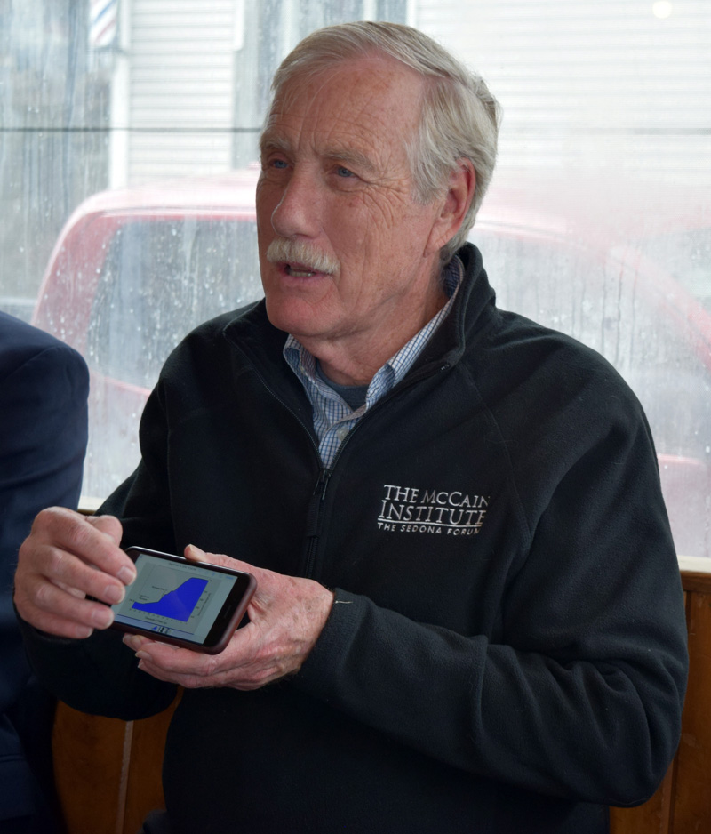 U.S. Sen. Angus King shows local officials a graph on his smartphone during a meeting about coastal resiliency at Sarah's Cafe in Wiscasset on Friday, April 27. (J.W. Oliver photo)
