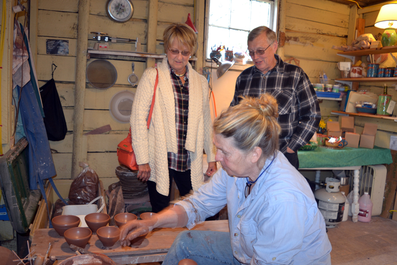 "Cindy and Bill Anderson, who split their time between Palm Coast, Fla. and Spruce Head, watch as Libbey Seigars demonstrates the Japanese pottery-making style of ""throwing from the mound"" at Whitefield Pottery on Sunday, May 6 during the Maine Pottery Tour. (Christine LaPado-Breglia photo)"