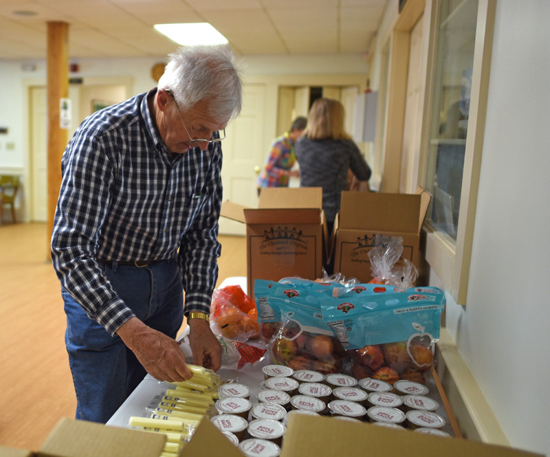Gordon Davis, a member of the Rotary Club of Damariscotta-Newcastle, sets snacks out for the Ecumenical Food Pantry's backpack program Friday, May 25. (Jessica Picard photo)