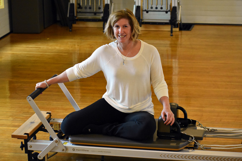Jessica Daly sits on a Pilates reformer at Ocean Blue Pilates Yoga, her new studio in the former Nobleboro Grange meeting hall. (Alexander Violo photo)
