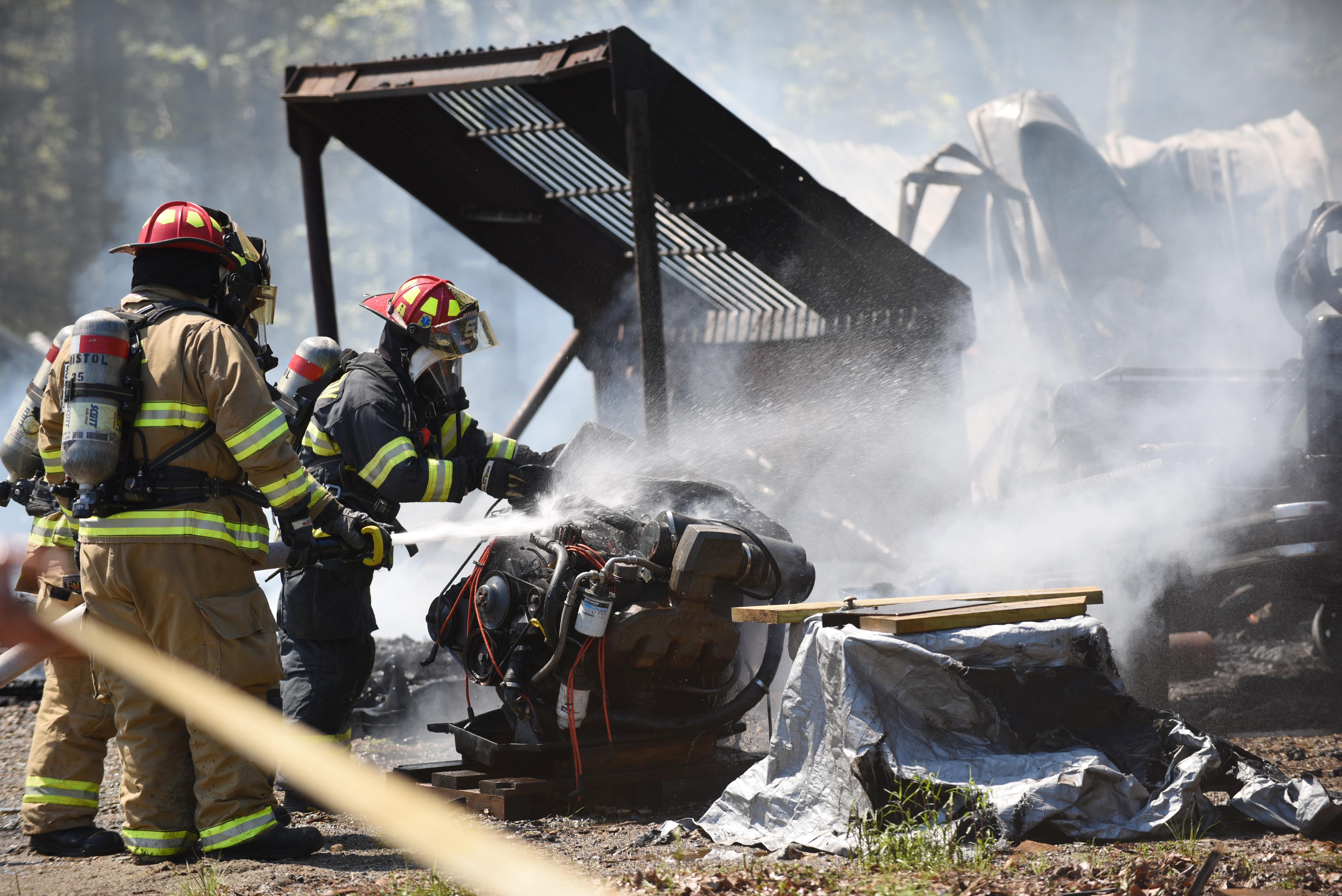 Firefighters spray a piece of equipment at a workshop fire on Wiley Woods Way in Walpole on Monday, May 21. (Jessica Picard photo)
