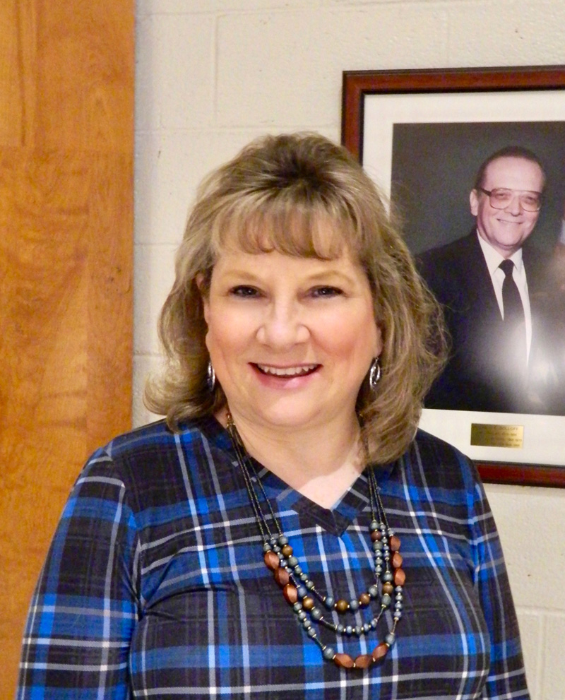 Linda Pease poses in front of a photo of her father, the late Ronald Doloff, Medomak Valley High School principal from 1970-1994. Pease will begin the same job in July after six months in an acting role. (Photo courtesy Lisa Genthner Gunn)
