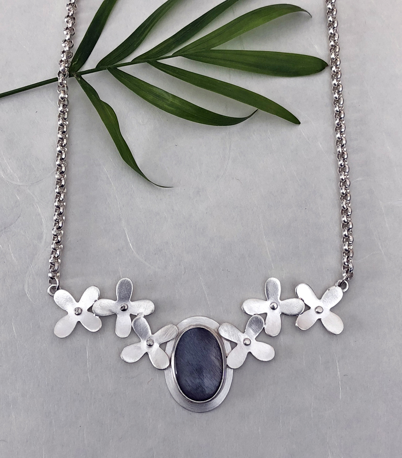A silver-flower moonstone necklace chain by Christine Peters.