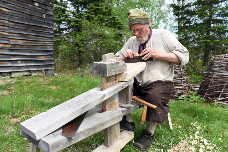 Jeff Miller, a tour guide and costumed interpreter at the Colonial Pemaquid State Historic Site, works on building a stool Friday, May 25. (Jessica Picard photo)