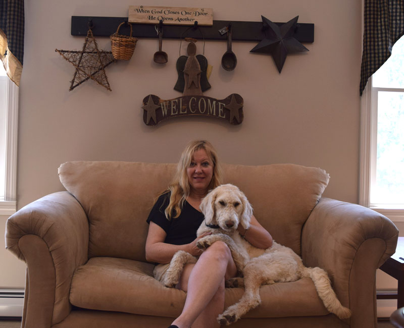Freedom Center Director Jan Burns sits with her dog, Sophie, in the center's gathering room. (Jessica Clifford photo)