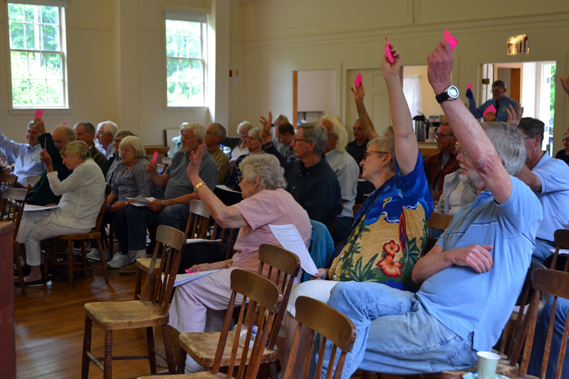 Westport Island voters raise their cards in favor of an article during annual town meeting at the historic town hall Saturday, June 23. Fifty-six voters attended the meeting. (Charlotte Boynton photo)