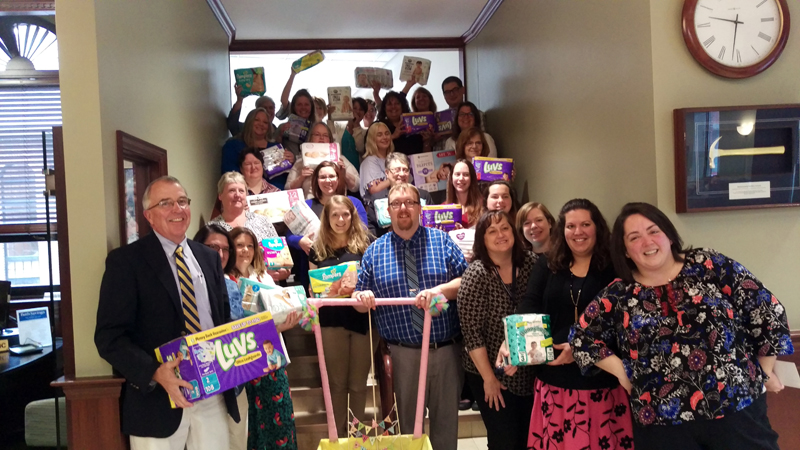 Glenn Hutchinson (left) president of Bath Savings, with Tina Magno (fourth from right), Jenny Little (right), and employees of the Bath Savings Institution's Bath office with diapers donated.