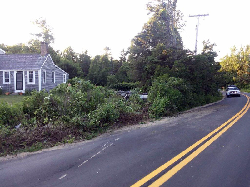 The scene of a Corvette crash near Pemaquid Point on Monday, July 9. The classic sports car is at rest on its roof on the lawn, partially obscured by roadside bushes. (Photo courtesy Lincoln County Sheriff's Office)