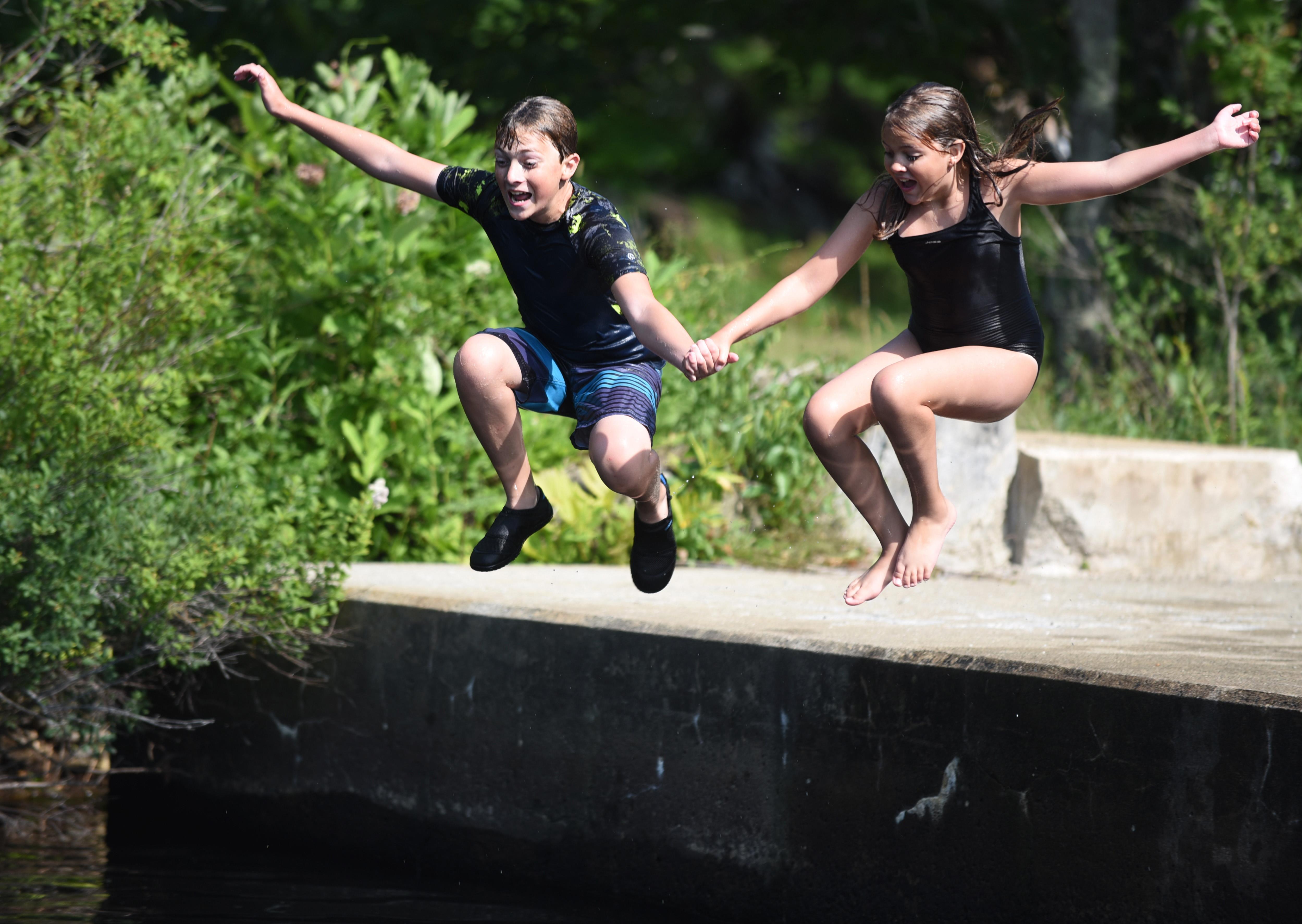 Logan Murff, 13, and Kellan Murff, 10, jump off the platform at the Bristol Mills Dam on Wednesday, July 11. (Jessica Picard photo)