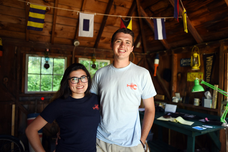 Madison Scarcella, 21, and Patrick Hile, 20, stand in the former boathouse now home to Hile's clothing business, Paul Landry Co., in Round Pond on July 10. (Jessica Picard photo)