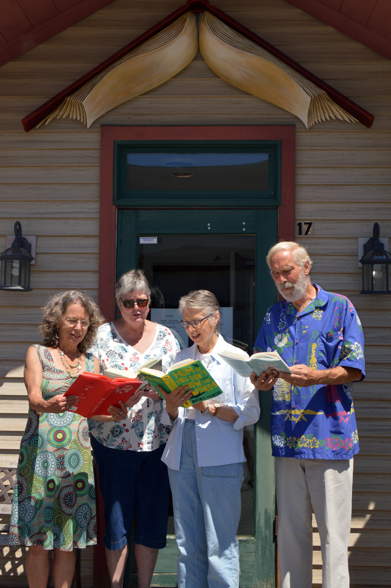 From left: Skidompha Secondhand Book Shop co-manager Rosie Bensen, Skidompha Library Executive Director Pam Gormley, longtime shop volunteer Janice Lindsay, and shop co-manager Rem Briggs pose with half-off novels during the shop's 50th anniversary celebration Saturday, July 21. (Johanna Neeson photo)