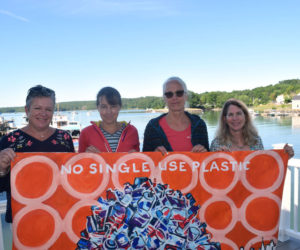 From left: kNOw S.U.P. members Ali Stevenson, Jenny Mayher, Adele Gale, and Co-chair Eleanor Kinney hold a painting on the deck outside the organization's meeting place in downtown Damariscotta. The painting illustrates the group's mission to reduce reliance on single-use plastics. (Jessica Clifford photo)