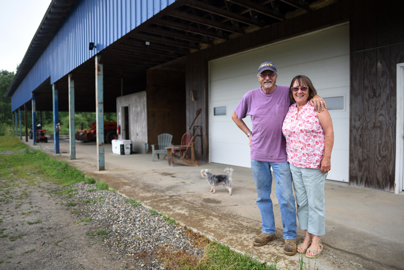 Jeff and Linda Biden stand in front of their former cattle barn, which they plan to use for automobile storage, Monday, July 23. (Jessica Picard photo)
