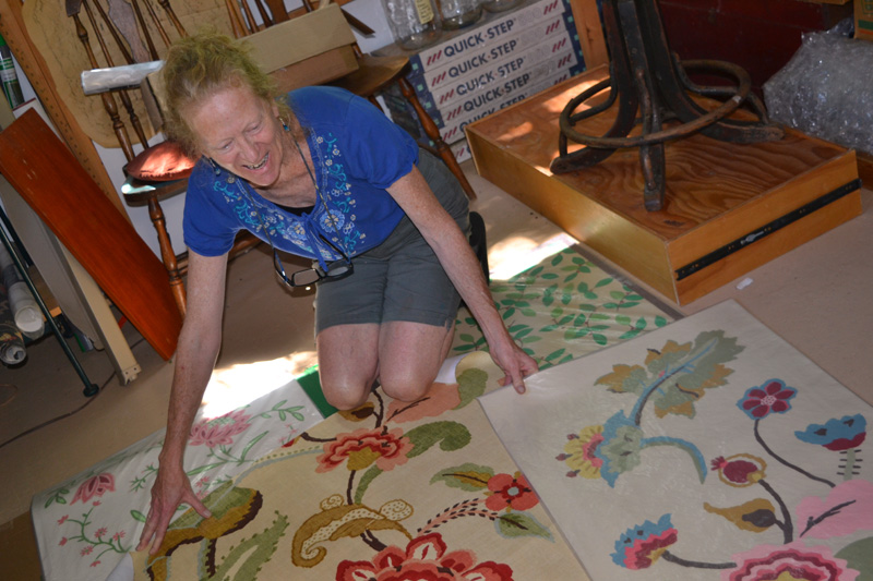 Walpole artist Susan Connery with her floorcloth designs in her studio. (Christine LaPado-Breglia photo)