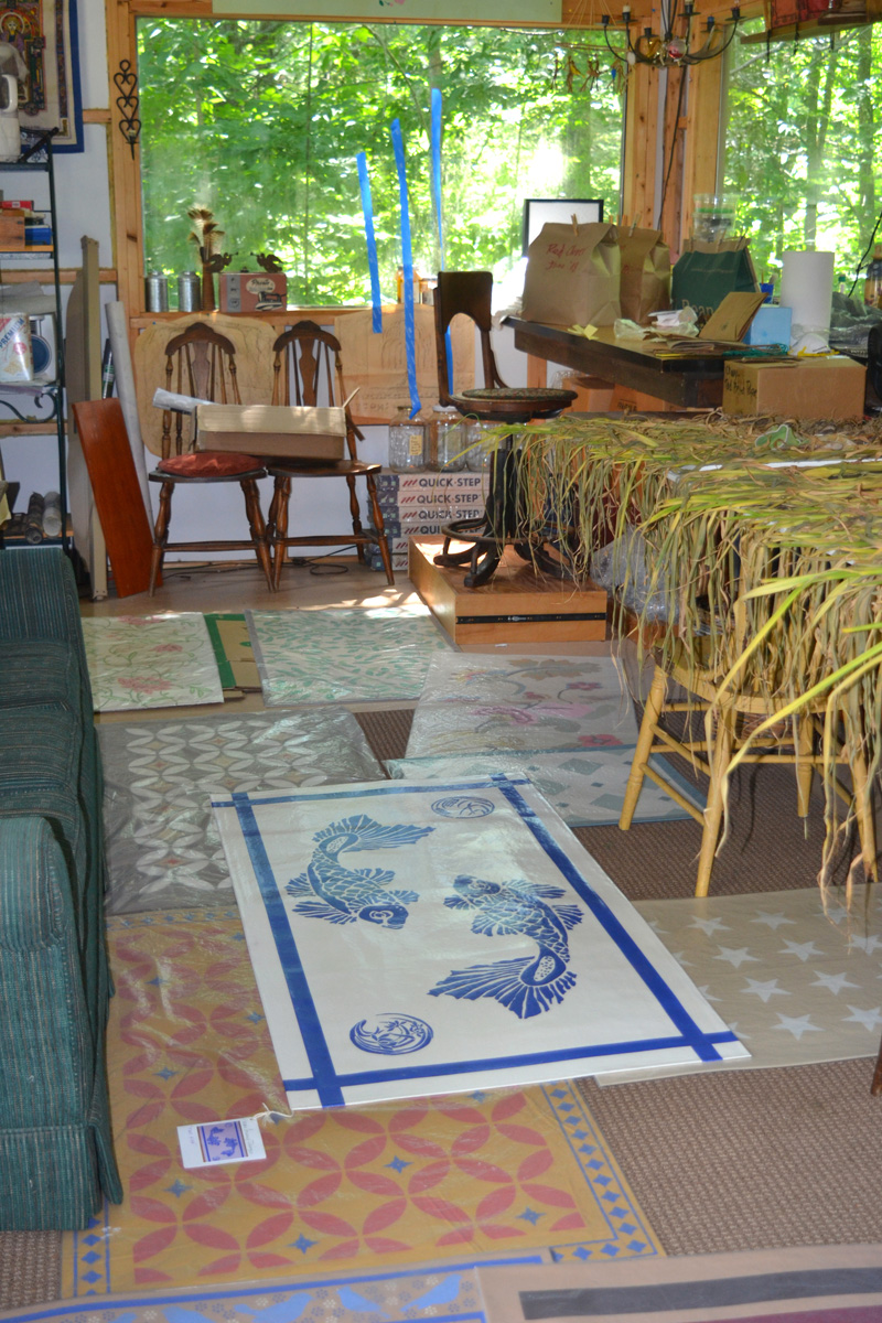 An array of Susan Connery Designs floorcloths share space with drying garlic in Susan Connery's Walpole studio. (Christine LaPado-Breglia photo)