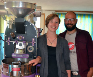 Monhegan Coffee Roasters co-owners Carley Mayhew and Mott Feibusch stand next to their coffee roaster in the business's headquarters on Monhegan Island. (Maia Zewert photo)