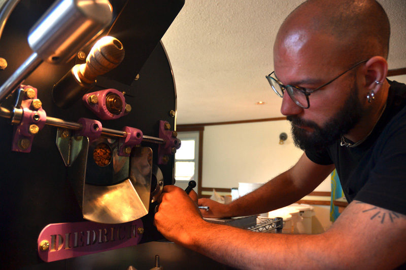 Monhegan Coffee Roasters co-owner Mott Feibusch checks the color of coffee beans during the roasting process. (Maia Zewert photo)