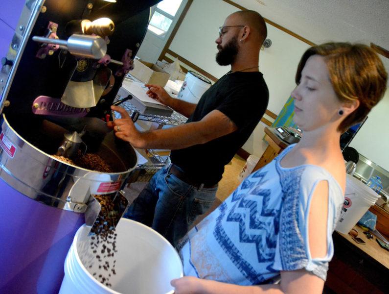 Carley Mayhew transfers coffee beans into a bucket after roasting while Mott Feibusch keeps an eye on a new batch at Monhegan Coffee Roasters. (Maia Zewert photo)