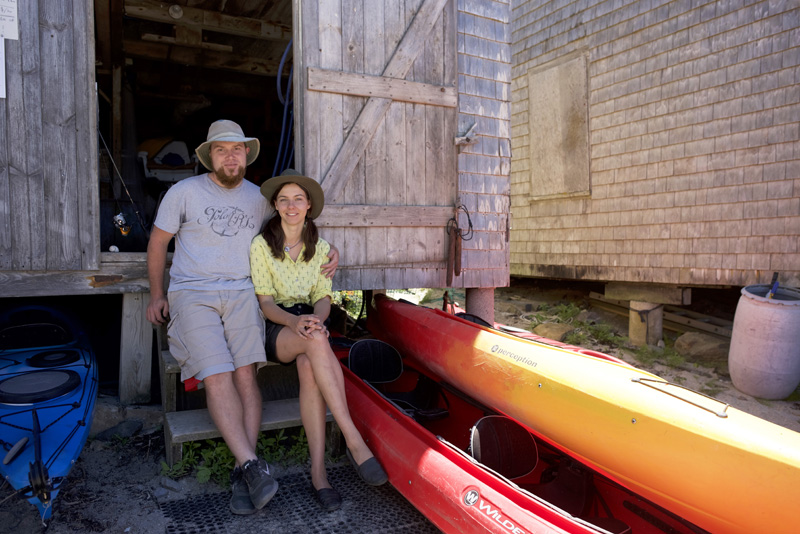 Tristan and Ola Vis, managers of Monhegan Kayak Rentals, sit on the steps of the shop Friday, June 22. (Jessica Picard photo)