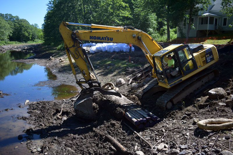 An excavator removes the remnants of a carriage road at the Coopers Mills Dam site Thursday, July 19. The contractor will remove the dam soon. (Jessica Clifford photo)